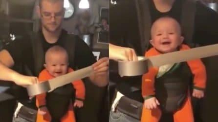 Il padre gioca con lo scotch, la reazione del bimbo è esilarante