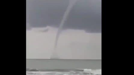 Improvviso temporale in spiaggia: la tromba marina si avvicina alla costa