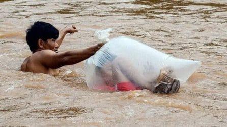 Bambini chiusi in sacchi di plastica, vengono trasportati dall'altra parte del fiume
