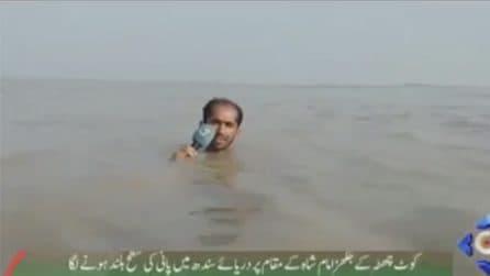 Con l'acqua fino alla gola per realizzare il servizio: il giornalista in diretta tv