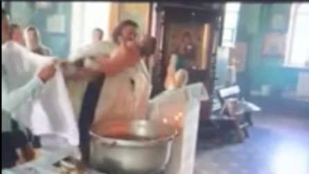 Battesimo violento: il prete immerge con forza il bambino nell'acqua, la mamma cerca di intervenire