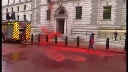 """Londra, ambientalisti spruzzano """"sangue"""" contro il ministero delle finanze. Protesta finisce male"""