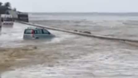 Il livello del mare si alza e invade le strade: un'auto viene sommersa
