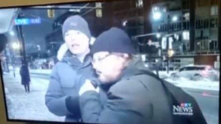 Il giornalista è in diretta, ma viene interrotto da un passante che gli toglie il microfono