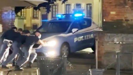 Volante della polizia incastrata tra le Colonne di San Lorenzo: gli agenti la spingono sotto la pioggia