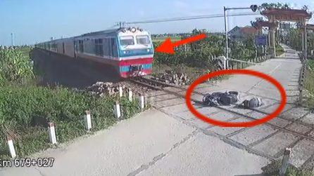 Cade con la moto e finisce sui binari mentre passa il treno
