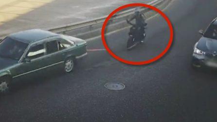 Motociclista si fa trainare da un'auto: quando affronta la curva accade un brutto imprevisto