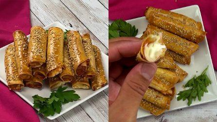 Rotolini di pasta sfoglia con prosciutto e formaggio: per un aperitivo filante e sfizioso!