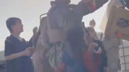 Soldati americani consegnano cibo ai bambini all'interno dall'aeroporto di Kabul