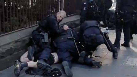Proteste anti-lockdown: 4 poliziotti bloccano un manifestante durante le proteste