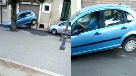 Auto resta incastrata e sollevata: l'uomo a bordo non sa come uscirne